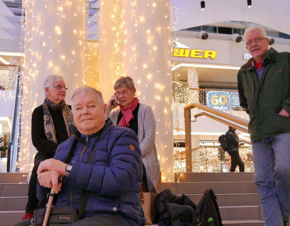fyra äldre personer sitter tillsammans på en trappa inomhus