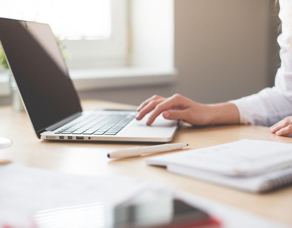 en kvinna som jobbar med en bärbar dator