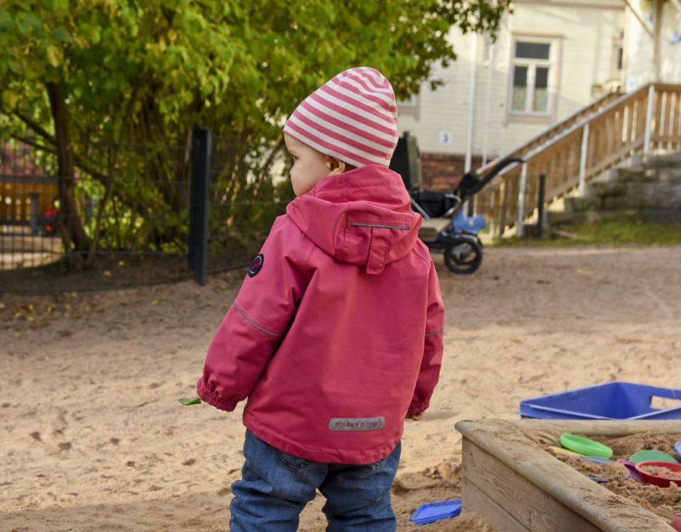 ett dagisbarn har ryggen vänd mot kameran