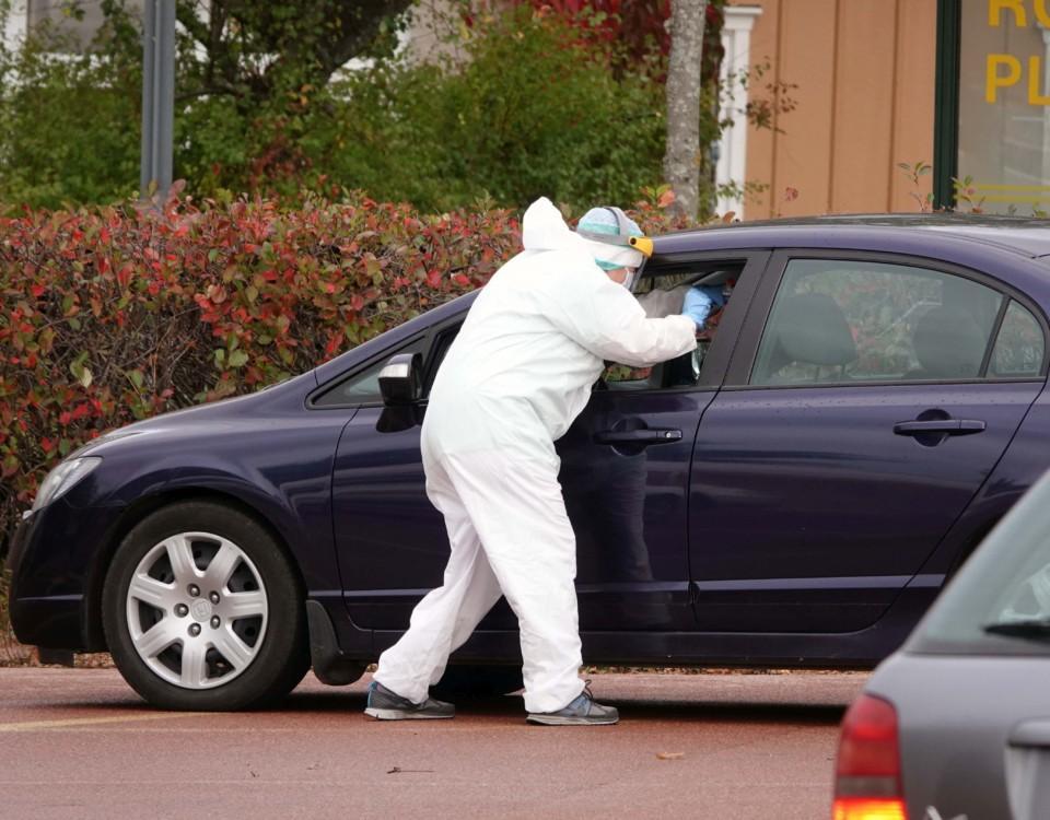 Person i skyddsutrustning vid en bil.