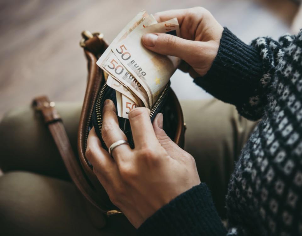 Händer tar ut pengar ur en plånbok