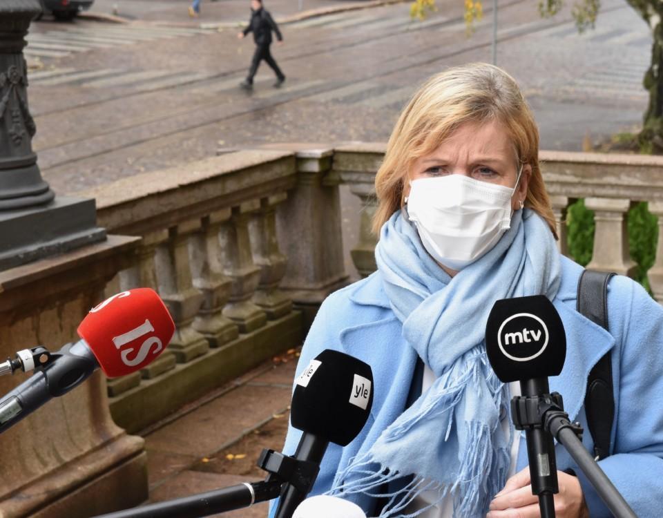 en kvinna med tre mikrofoner framför sig