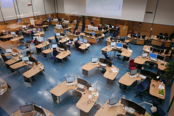 en massa skrivbord med datorn i en stor sal