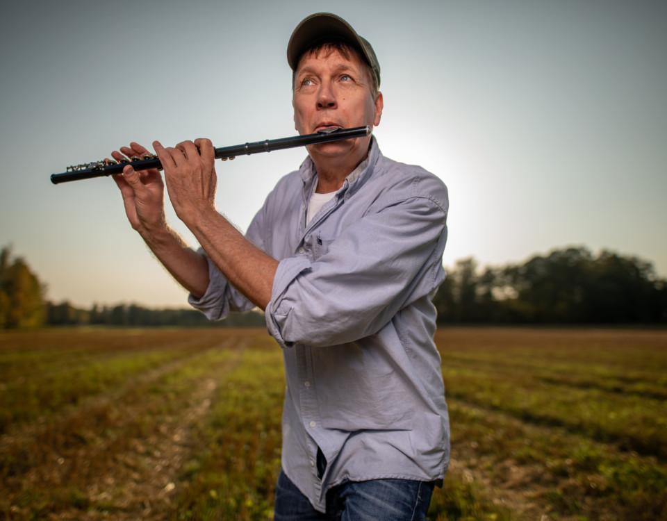 man spelar flöjt med ett åkerfält i bakgrunden