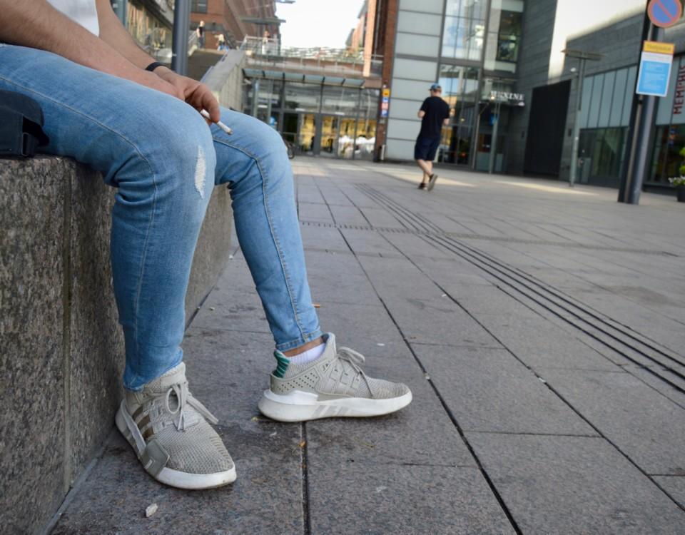 Ungdom som sitter på en stenbänk.