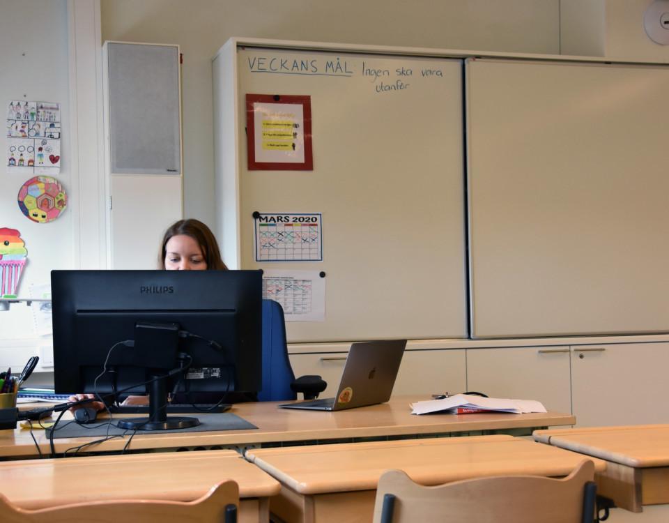 en lärare sitter bakom en datorskärm vid ett skrivbord