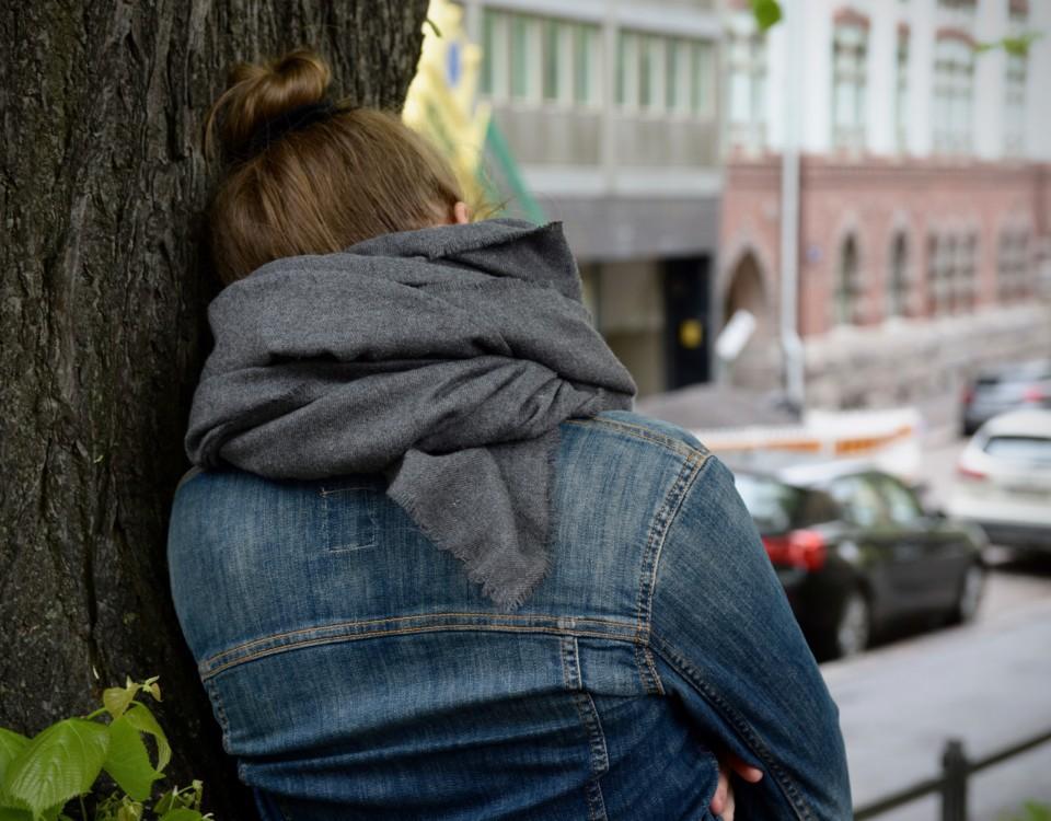 Människa lutar sig mot ett träd.