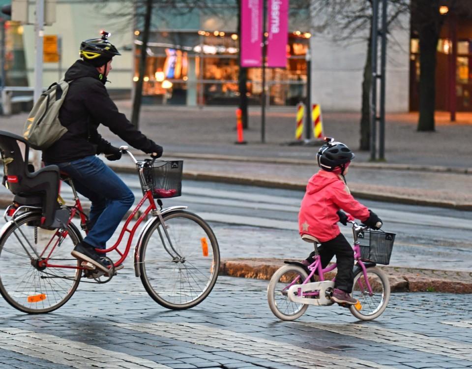 Far och dotter cyklar i trafik