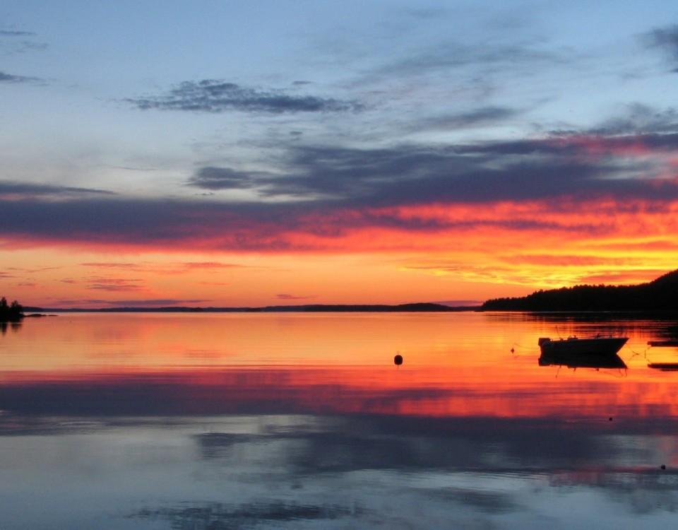 En solnedgång och en båt vid en boj.