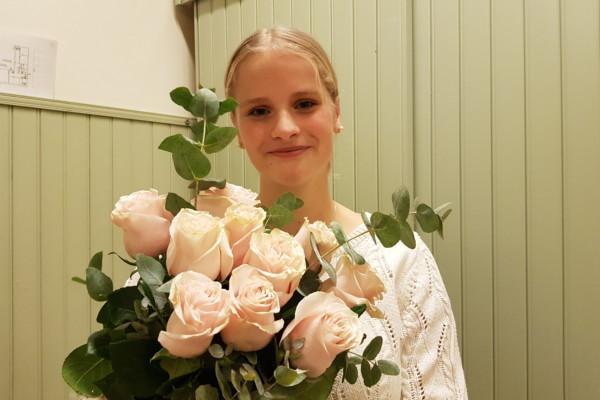 ljushårig ung kvinna med stor bukett ljusröda rosor