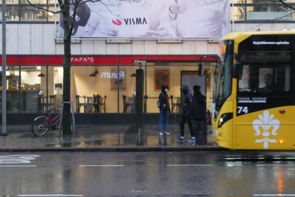 några personer står på en busshållplats och en buss kör in
