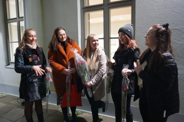 fem unga kvinnor står vid en husvägg med blommor i hand