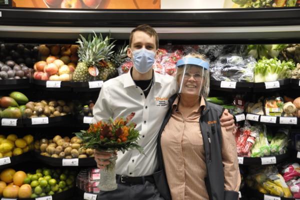Två personer i en affär. Håller om varandra. Bär munskydd/visir.