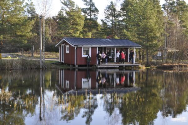 En liten stuga, med folk på terrassen, syns på andra sidan av en damm.