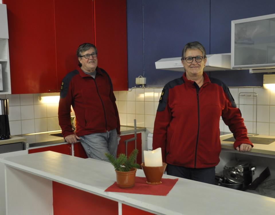 Två personer i ett nyrenoverat kök i färgerna blått, vitt och rött.