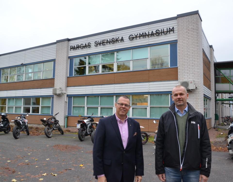 två män utanför en skolbyggnad