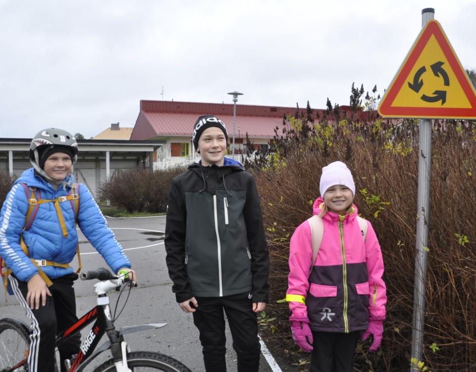 Tre barn vid ett minitrafikmärke som varnar om rondell