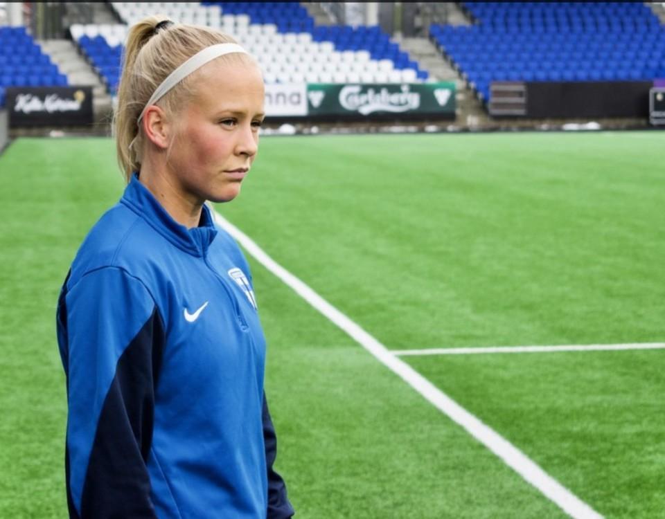 Adelina Engman vid sidlinjen i en tom fotbollstadion.