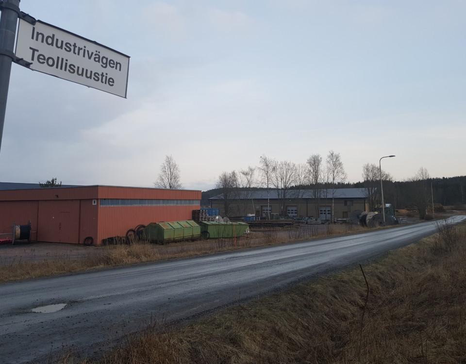 Grusväg genom ett litet industriområde