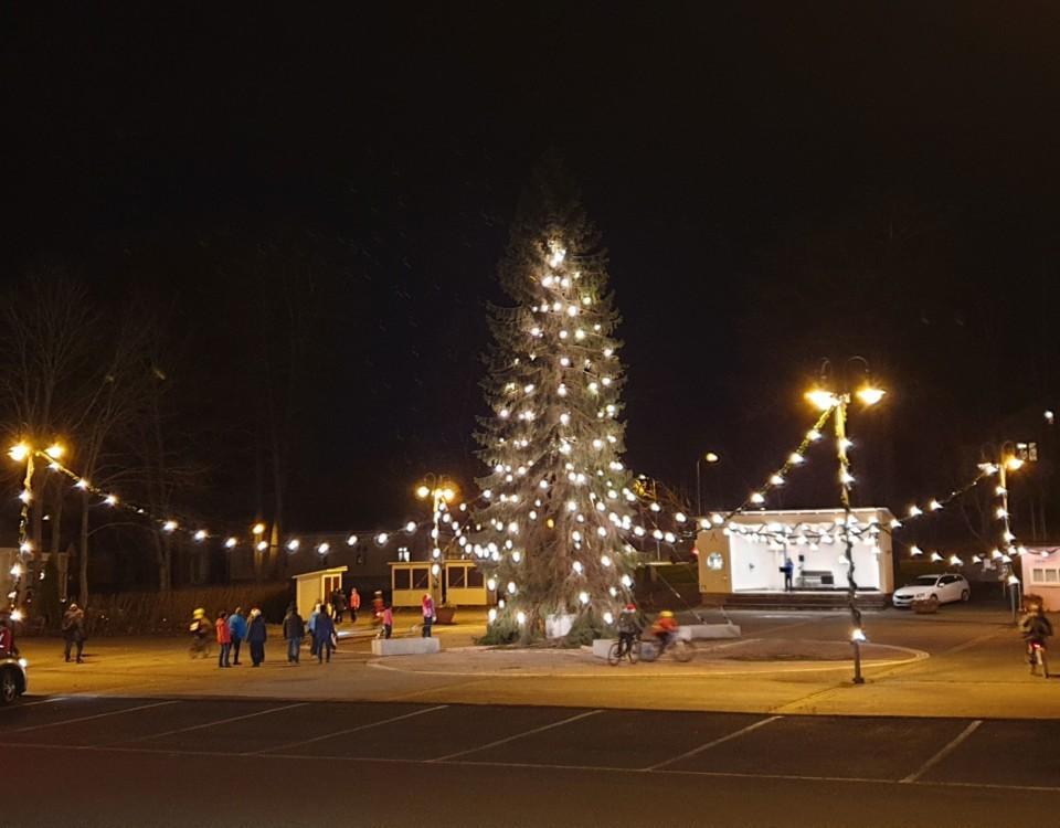 Julgran med lampor på ett torg