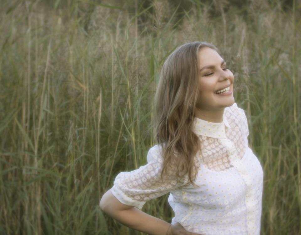 ung kvinna står på ett grönt fält och ler stort