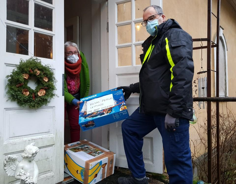Man och kvinna vid en öppnad dörr till bostadshus. Håller bägge i ett paket. De bär munskydd