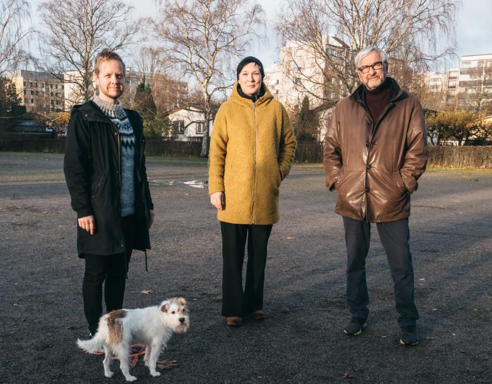 tre personer står på rad i morgonsol i park i bostadsområde
