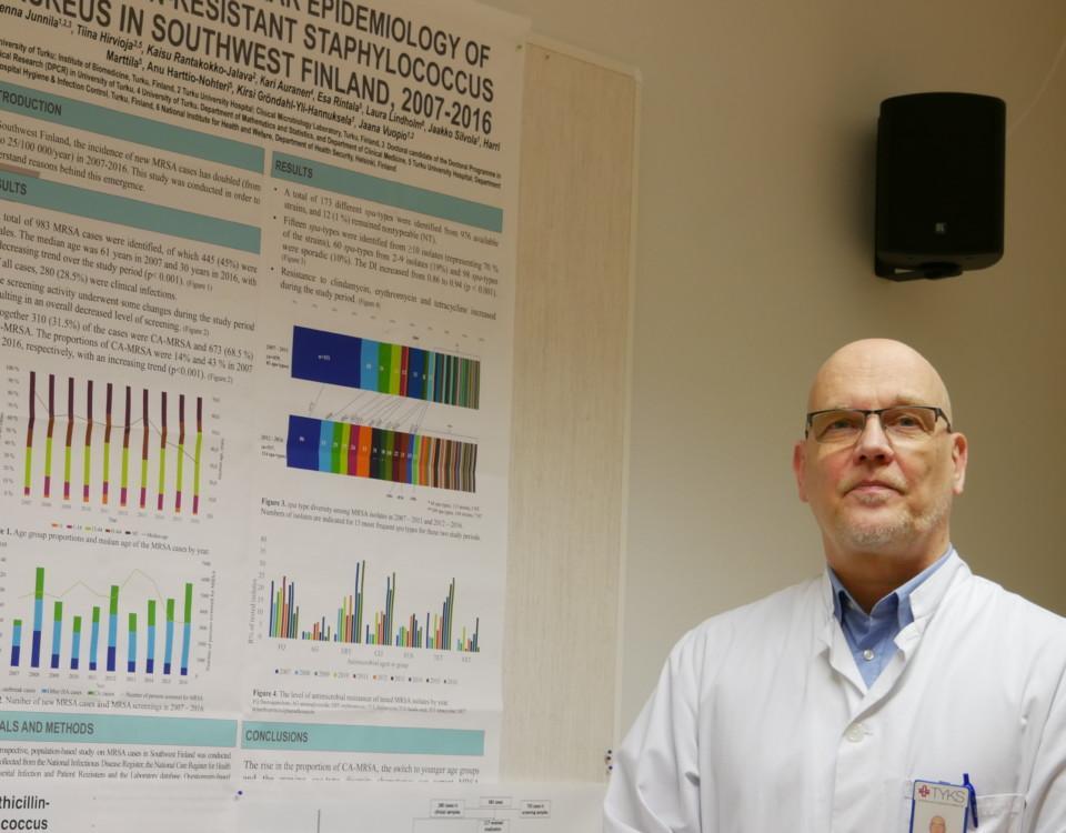 en läkare står bredvid en affisch med olika diagram på väggen