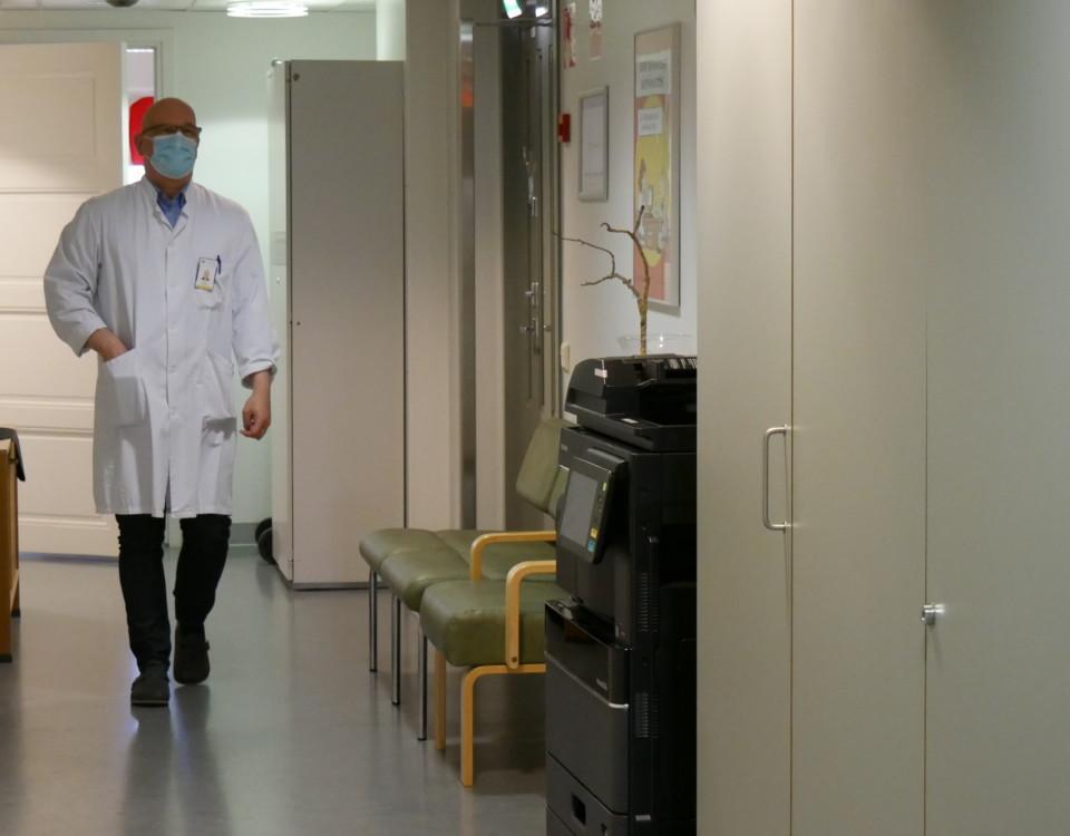 en läkare med munskydd promenerar i en korridor