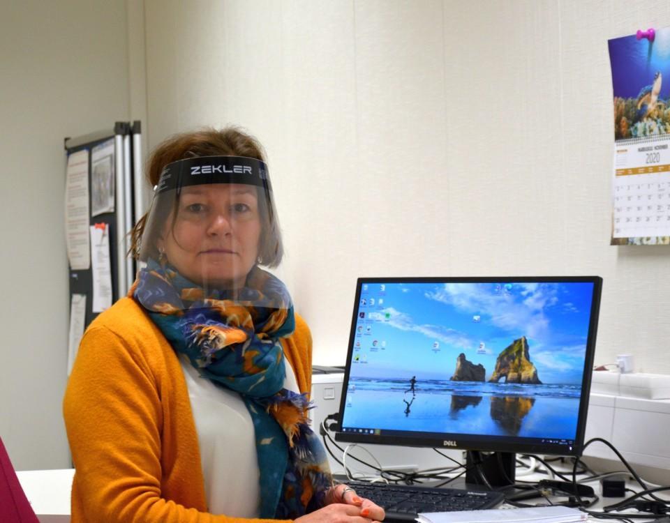 en kvinna iklädd visir vid ett arbetsbord