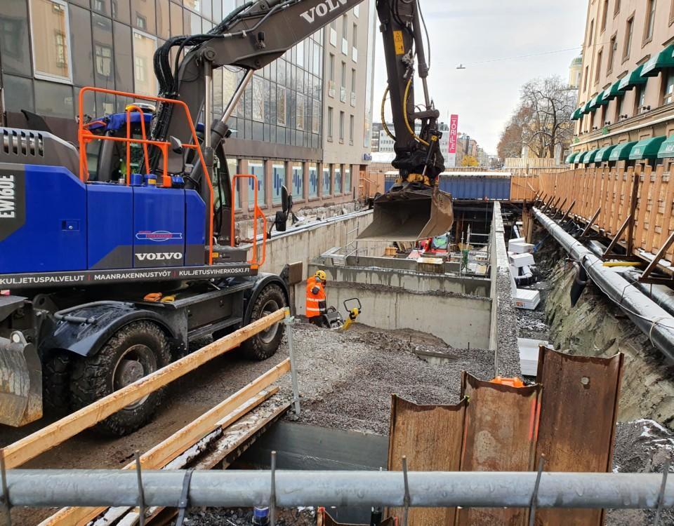 En grävmaskin och betongelement för något som kunde vara början till en körramp.