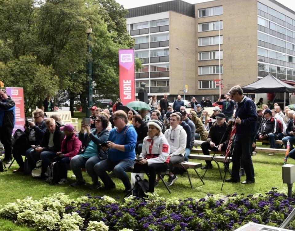 Parkmöte på en gräsmatta, folk sitter på bänkar.