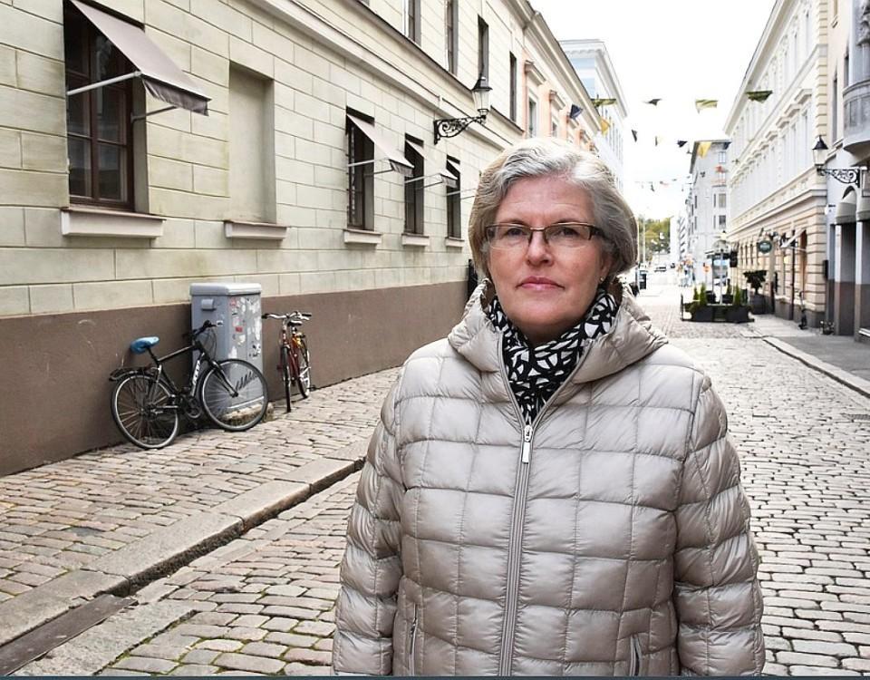 Katri Viinikka i grå jacka på en kullerstensgata i Helsingfors.