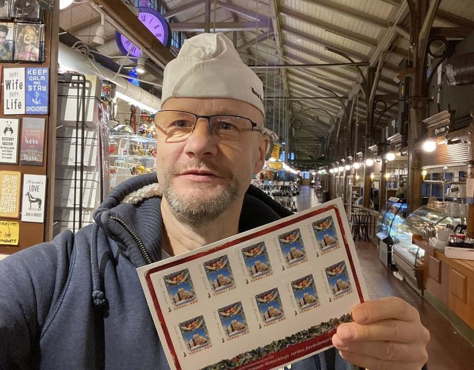 en man visar upp frimärken