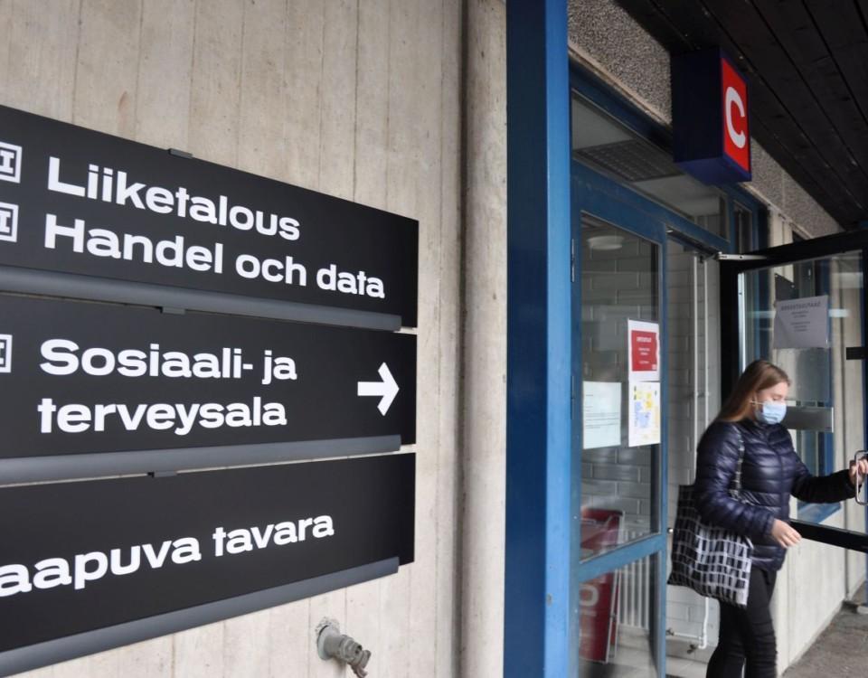 Kvinna kommer ut ur yrkesskolas dörr