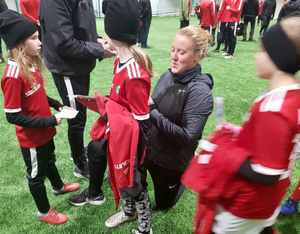 en fotbollsspelare omringad av autografjägare