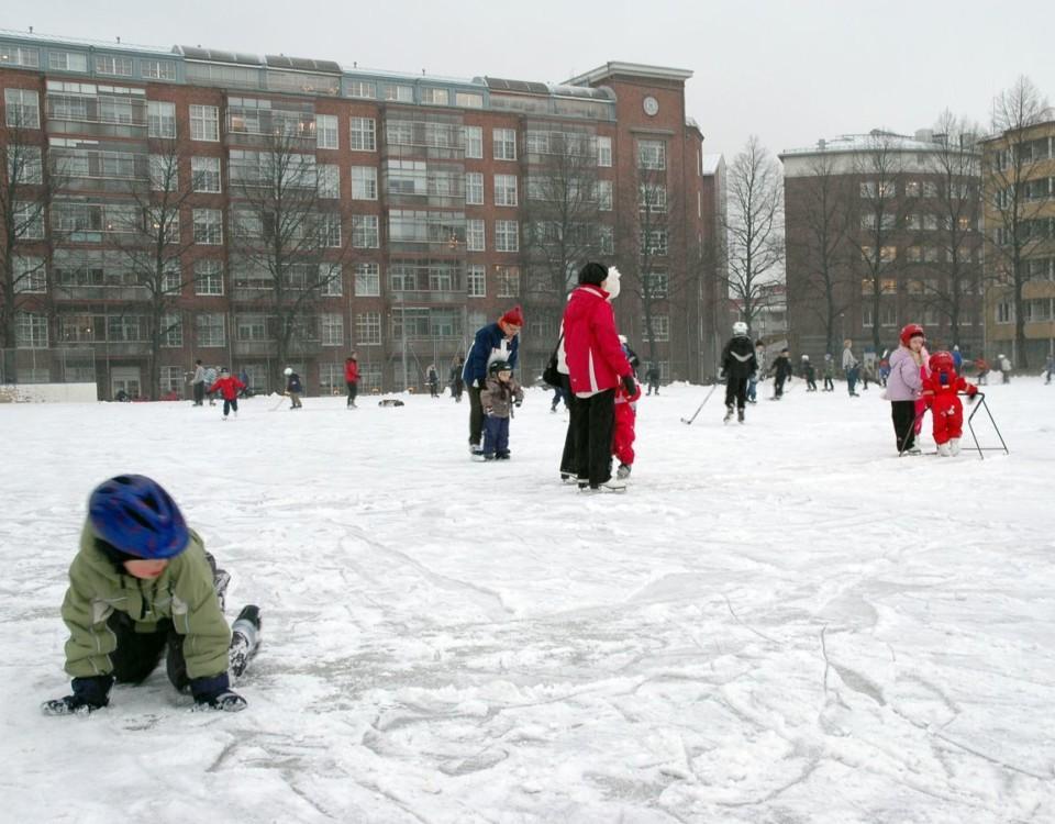 Barn åker skridsko på isbana i höghuskvarter