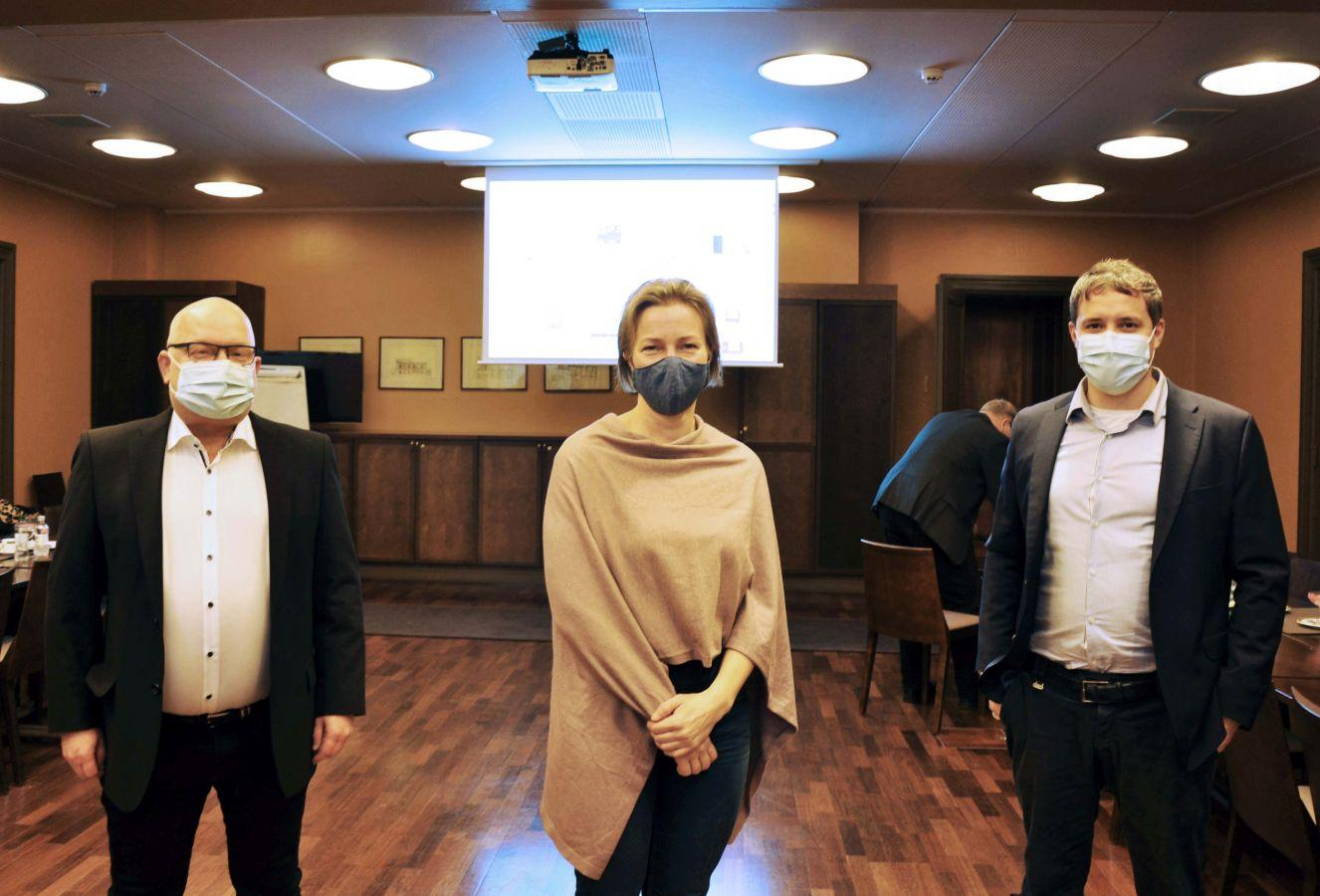 Tre personer med munskydd i mötessal