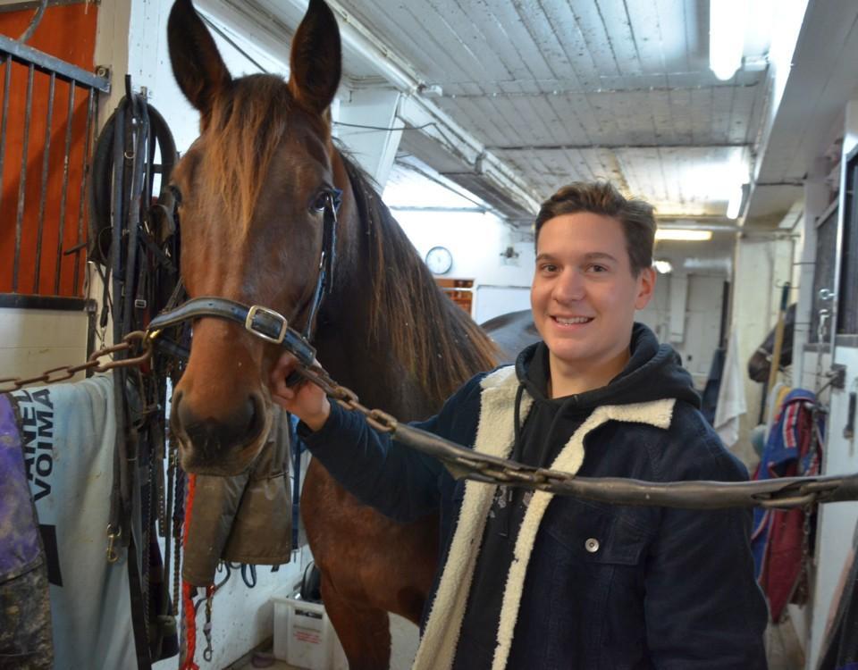 en man och en häst i ett stall