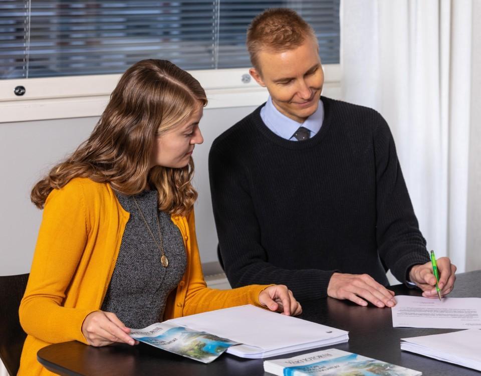 två glada, unga personer sitter vid ett bord och går igenom papper