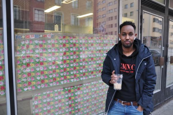 En mörkhyad man med en kaffekopp utanför ett kafé