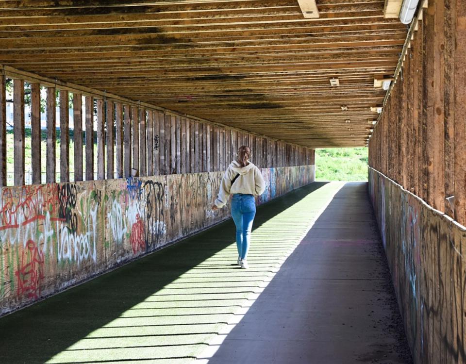 en ungdom som går i en nerklottrad korridor