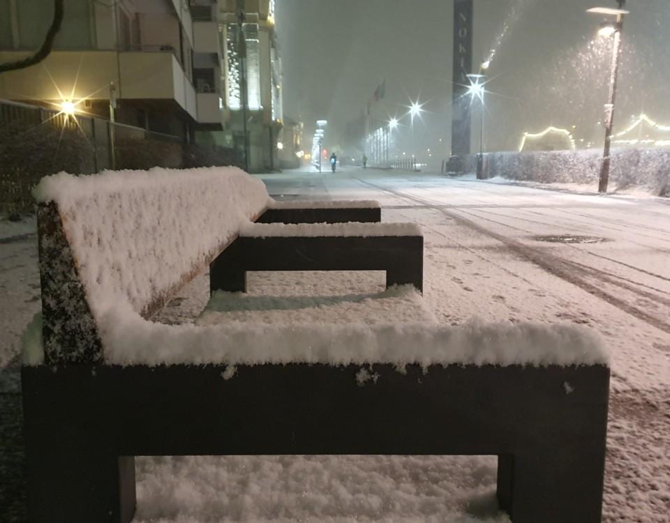 En parkbänk med snö på.