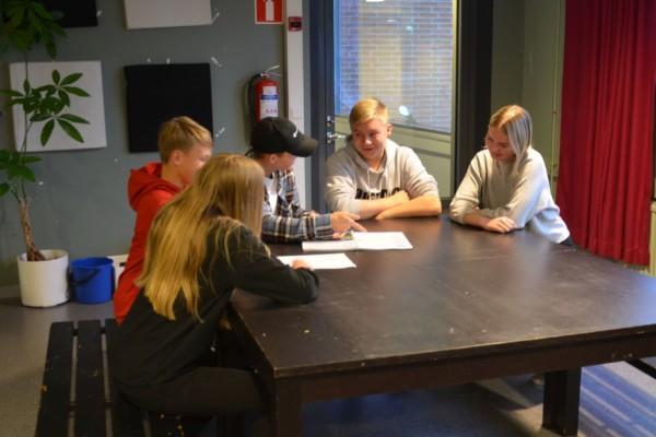 en grupp unga som sitter vid ett bord och diskuterar
