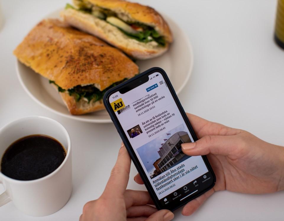 Hand som håller i en mobiltelefon. kaffe och en semla.