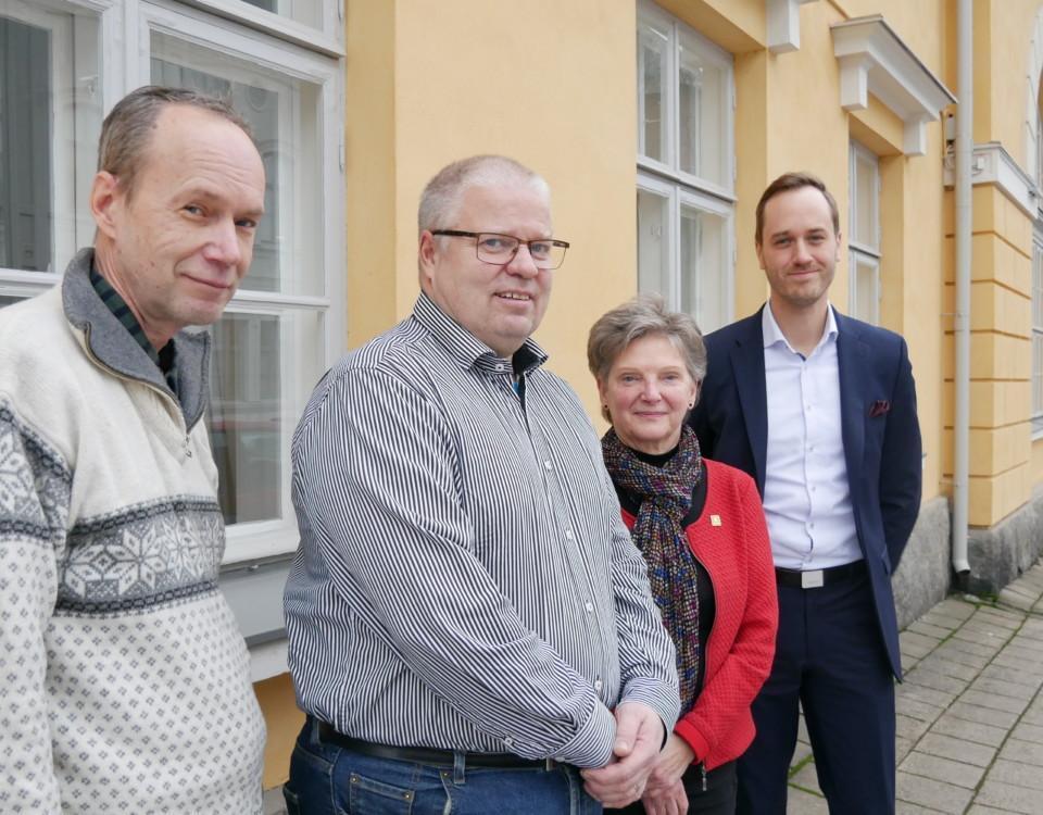 fyra personer poserar för kameran vid en gul yttervägg