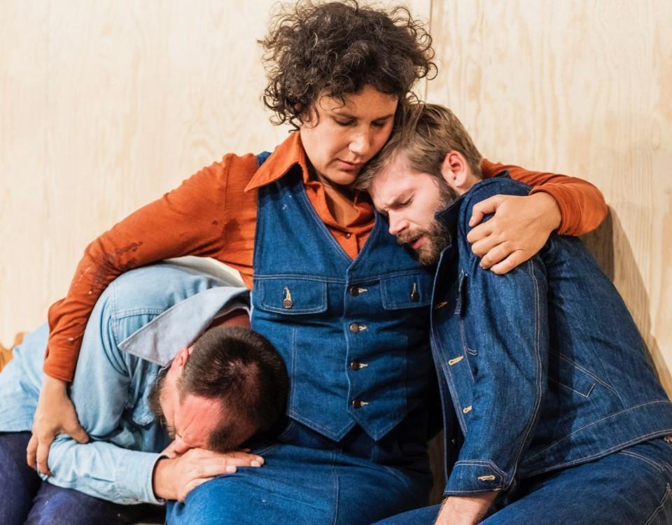 En kvinna som tröstar två män.
