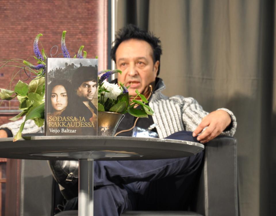 En man vid ett bord med blommor.