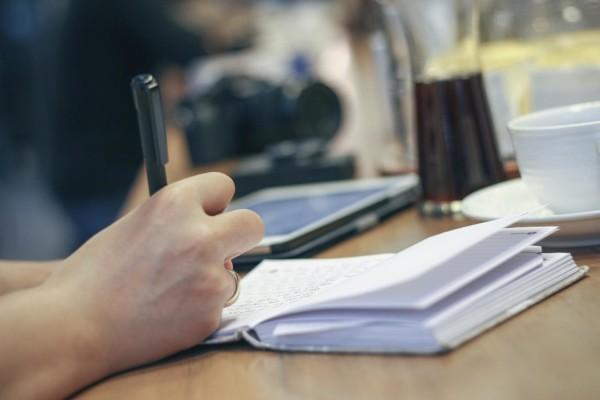 Hand som skriver i ett häfte.