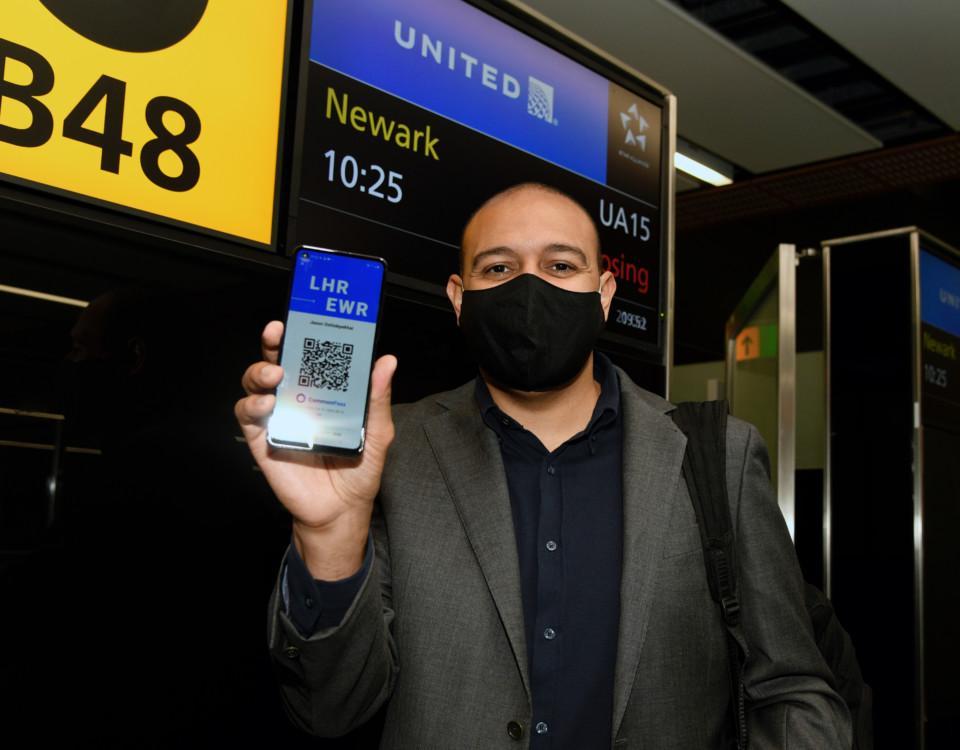 en man med en mobiltelefon med ett coronatest